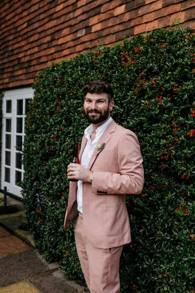 Groom in pink wedding suit at Micro wedding
