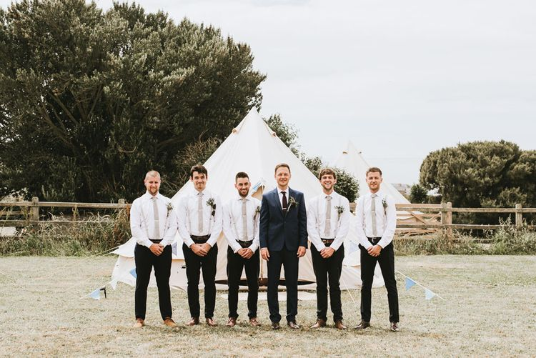 Groom and groomsmen in matching outfits for festival themed wedding