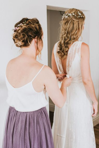Bride gets into her wedding dress with half up half down hairstyle
