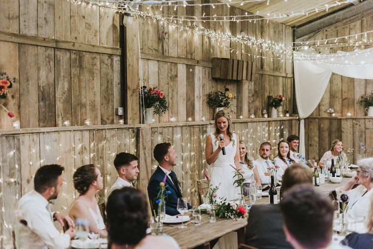 Bride speech at vegan wedding with fairy light backdrop