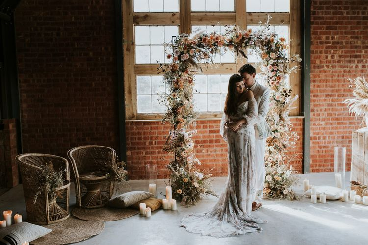 Bride and Groom in Front of Dried Flowers Arch in Rue de Seine Wedding Dress and ASOS Suit