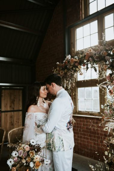 Bride and Groom Embracing Near Dried Flowers Floral Arch