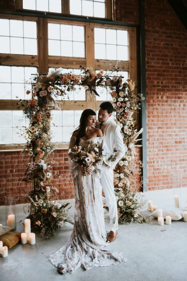 Bride and Groom Portrait in front of Dried Flowers Arch