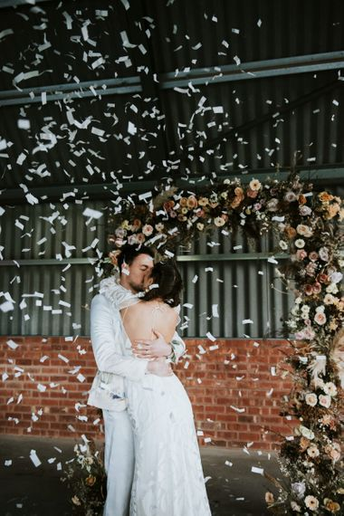 Bride and Groom Kissing Whilst Confetti Cannon Goes Off
