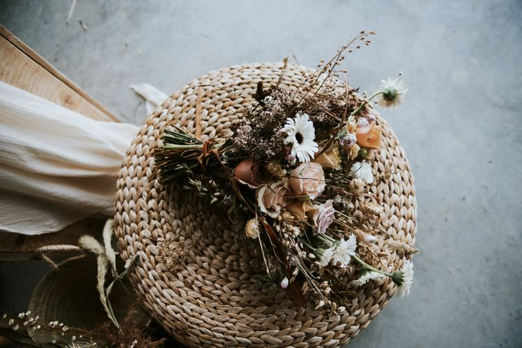 Wicker Chair with Peach, White and Dried Flowers Mixed in the Bouquet
