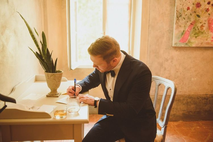 Groom on wedding morning writing a love note
