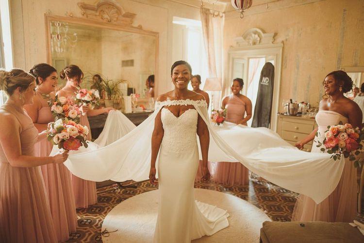 Bridesmaids helping the bride into her wedding cape