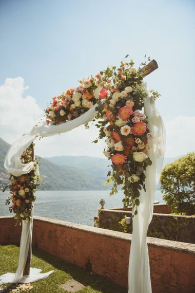 Wedding arch with, drapes and white and coral flowers