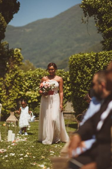 Bridesmaid in strapless dress walking down the aisle