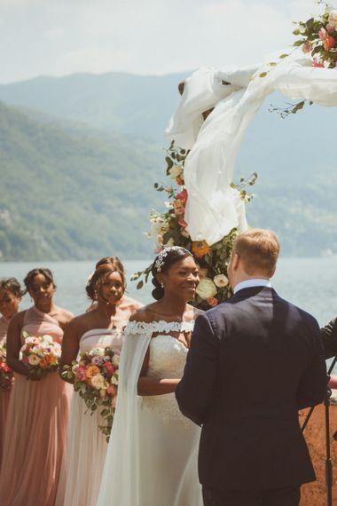 Bride smiling at her groom during wedding ceremony