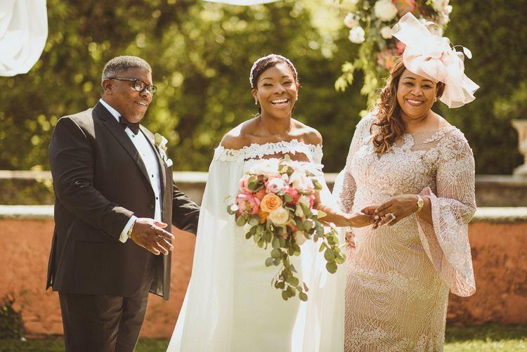 Bride in wedding cape with her parents