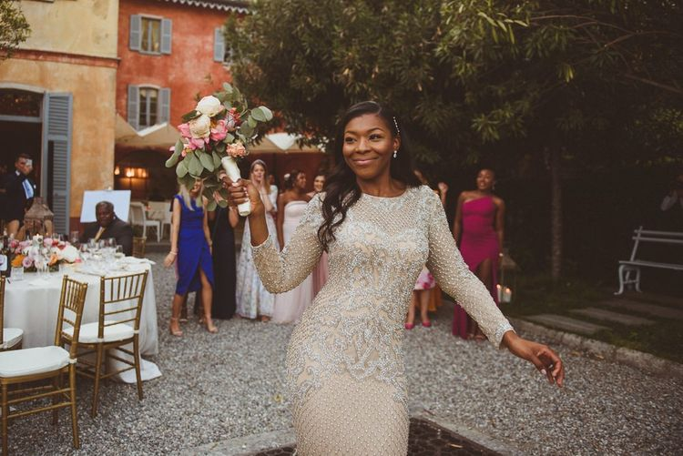 Bride in Gold sequin evening gown tossing her bouquet