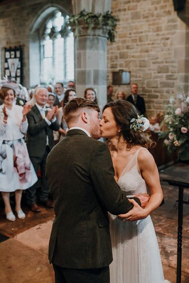 Ceremony. Tipi Wedding at Home, Cumbria. Pale Dusky Pink, White and Mocha Flowers, Handwritten Details and Festoon Lights. Bride wears Essence of Australia Dress from Angelica Bridal. Groom wears Olive Next Suit and Tan Office Shoes.