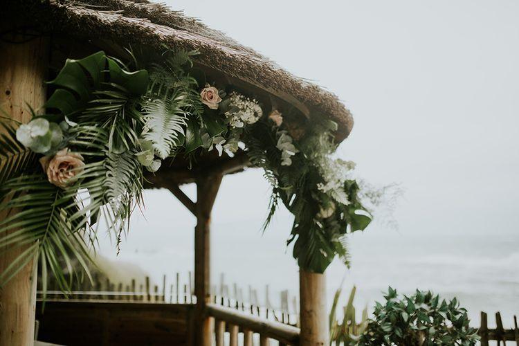 Foliage and Fern Covered Beach Hut