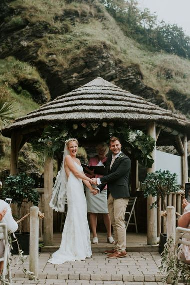 Coastal Wedding Ceremony at Tunnels Beaches in Devon with Bride in Lace in Willowby by Watters Wedding Dress and Groom in Chino's and Blazer
