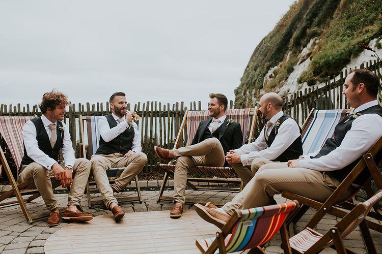 Groomsmen Sitting On Deck Chairs