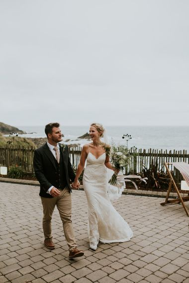Bride in Lace Willowby by Watters Wedding Dress and Groom in Chino's and Blazer Holding Hands