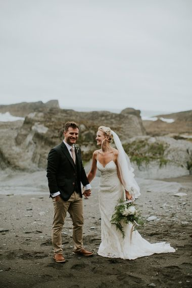 Bride in Lace Willowby by Watters Wedding Dress and Groom in Chino's and Blazer Holding Hands on the Beach