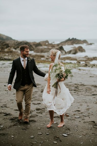 Bride in Lace Willowby by Watters Wedding Dress and Groom in Chino's and Blazer Walking on the Beach