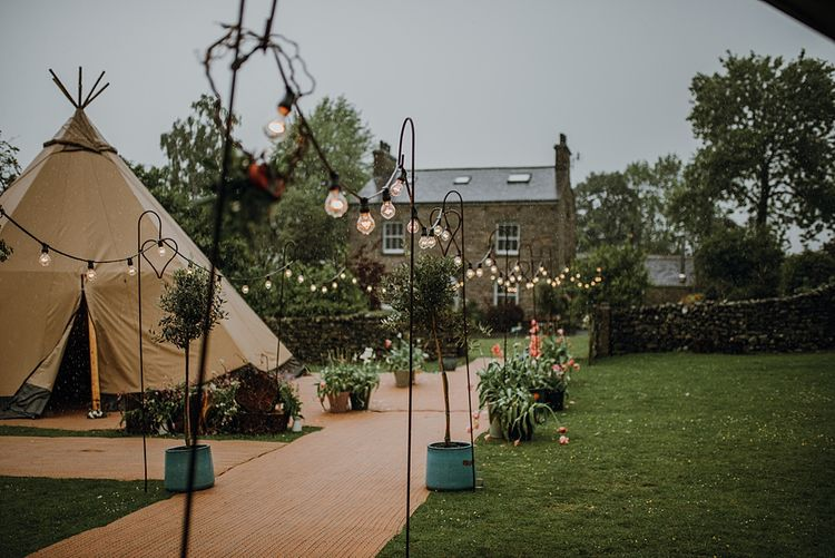 Festoon lIghts on Shepherds Crooks. Tipi Wedding at Home, Cumbria. Pale Dusky Pink, White and Mocha Flowers, Handwritten Details and Festoon Lights. Bride wears Essence of Australia Dress from Angelica Bridal. Groom wears Olive Next Suit and Tan Office Shoes.
