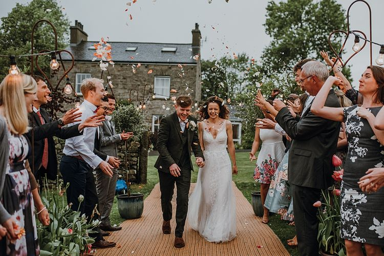Confetti Entrance to Reception. Tipi Wedding at Home, Cumbria. Pale Dusky Pink, White and Mocha Flowers, Handwritten Details and Festoon Lights. Bride wears Essence of Australia Dress from Angelica Bridal. Groom wears Olive Next Suit and Tan Office Shoes.