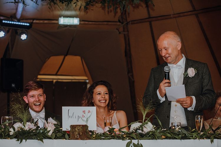 Speeches. Tipi Wedding at Home, Cumbria. Pale Dusky Pink, White and Mocha Flowers, Handwritten Details and Festoon Lights. Bride wears Essence of Australia Dress from Angelica Bridal. Groom wears Olive Next Suit and Tan Office Shoes.