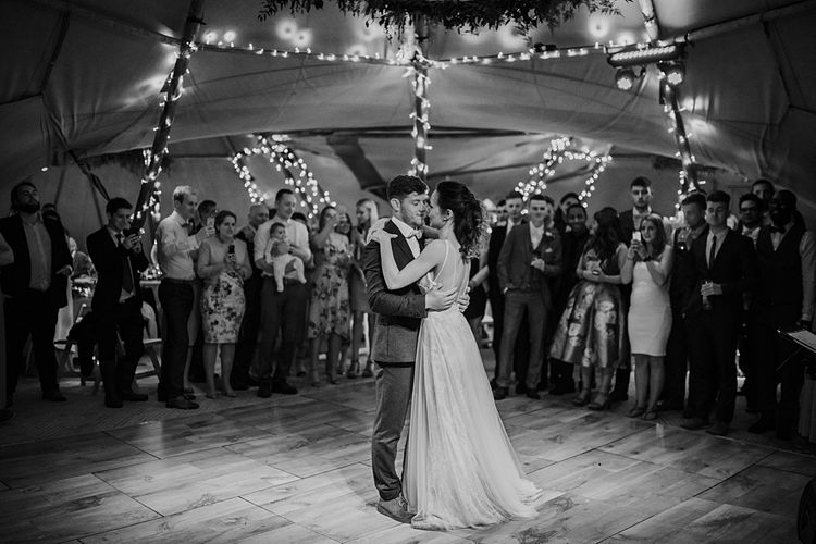 Dancing. Tipi Wedding at Home, Cumbria. Pale Dusky Pink, White and Mocha Flowers, Handwritten Details and Festoon Lights. Bride wears Essence of Australia Dress from Angelica Bridal. Groom wears Olive Next Suit and Tan Office Shoes.