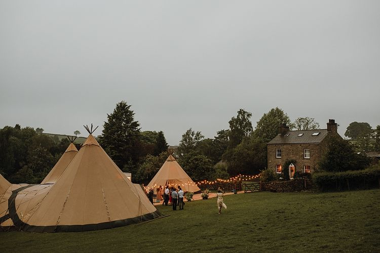 Tipi Wedding at Home, Cumbria. Pale Dusky Pink, White and Mocha Flowers, Handwritten Details and Festoon Lights. Bride wears Essence of Australia Dress from Angelica Bridal. Groom wears Olive Next Suit and Tan Office Shoes.