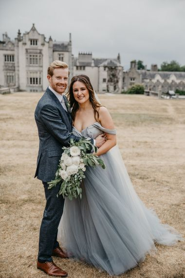 Bride in Custom Made Claire La Faye Wedding Dress and Groom in Bespoke Alton Lane Suit Embracing