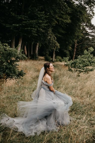 Bride in Custom Made Blue Claire La Faye Wedding Dress Twirling in the Grass