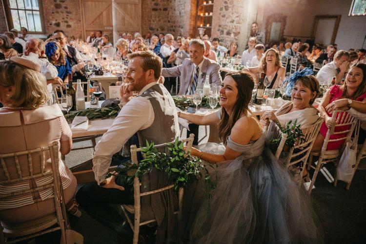 Bride and Groom Enjoying the Wedding Reception Speeches