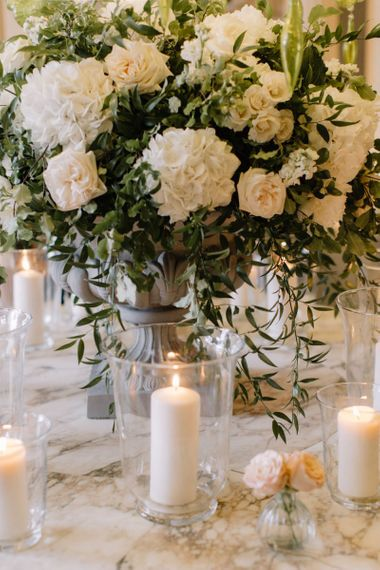 White wedding flowers and candles in hurricane vases