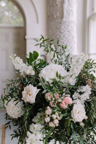 White and pink wedding flower arrangements with foliage