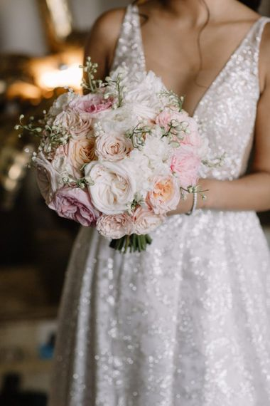 Bride in Berta Bridal gown holding a romantic blush pink and white wedding bouquet with David Austin roses