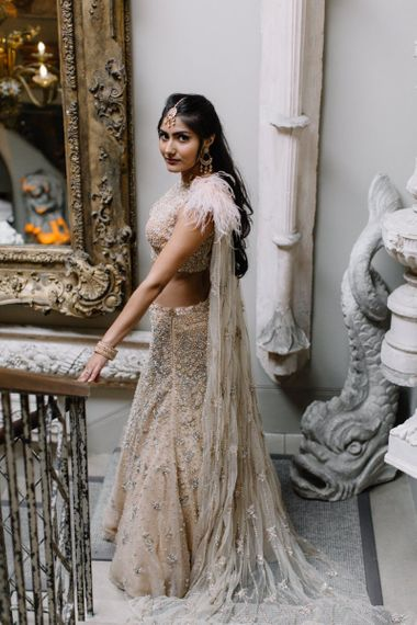 Bride in gold and blush Indian separates with feathers and cape