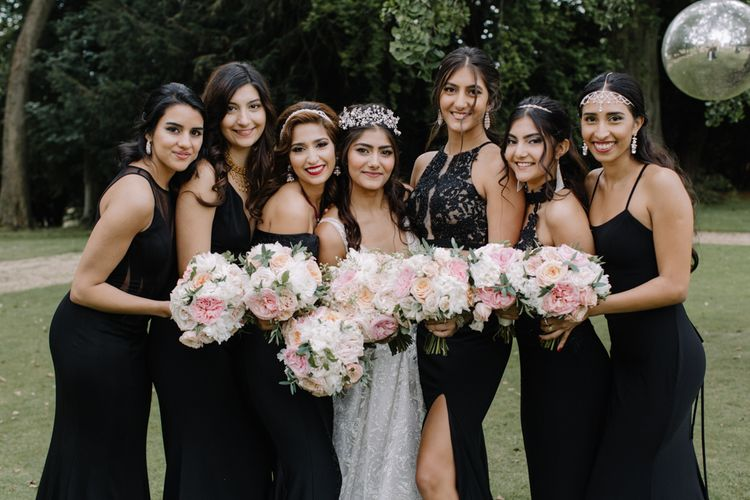 Bridal party portrait with bridesmaids in black dresses and bride in Berta Bridal gown