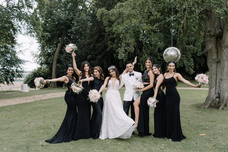 Bride and groom with bridesmaids at black-tie wedding with Berta Bridal gown