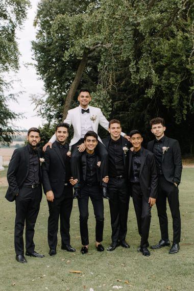 Groomsmen in black shirts and suits and groom in white dinner jacket