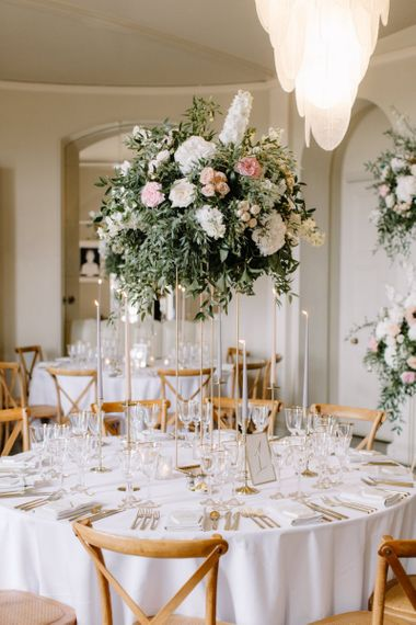 Blush pink and white floral centrepiece on high gold stand