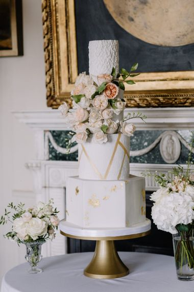 Luxury wedding cake with gold detail and blush wedding flowers