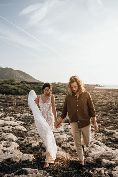 Boho bride and groom holding hands on the beach at Mallorca wedding