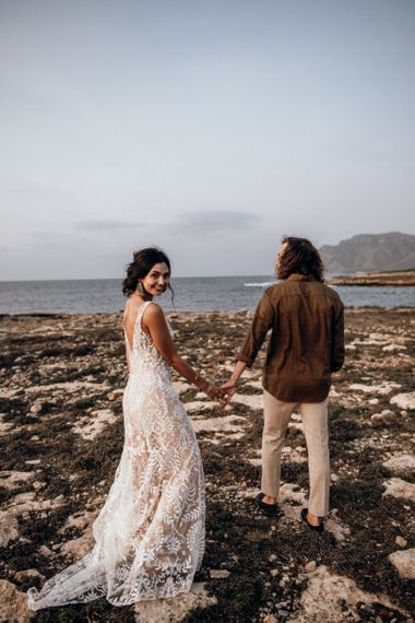 Boho bride and groom holding hands at the beach