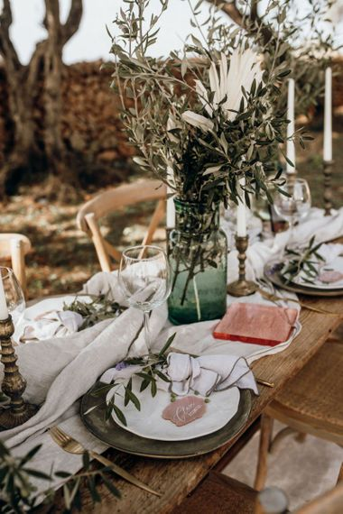 Wedding table decor with green glass, pink acrylic signs and white linens