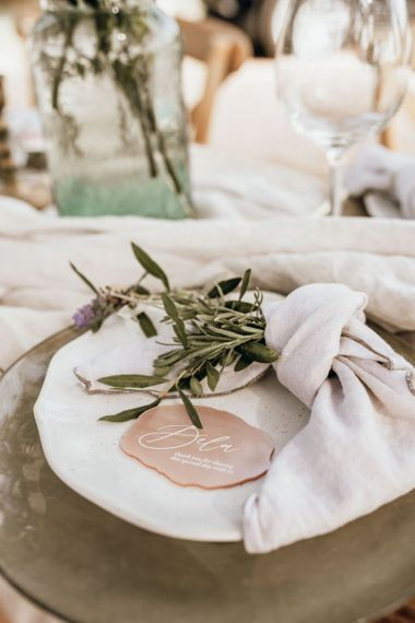 Place setting with linens, foliage and pink place name card