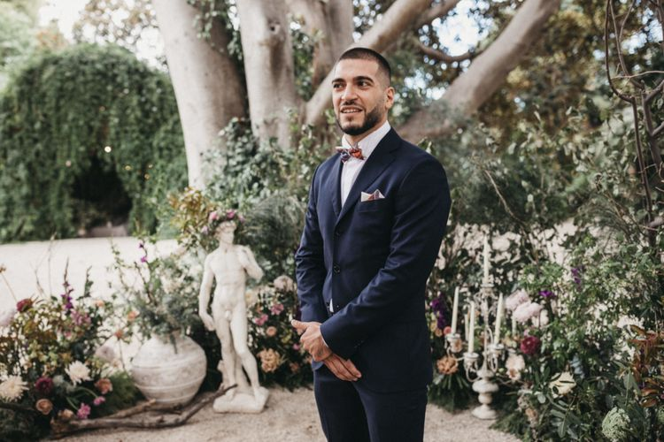Groom in navy wedding suit with bowtie
