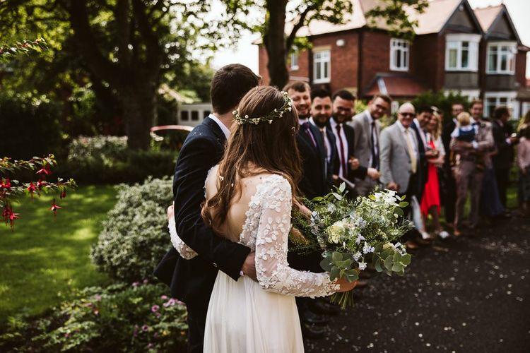 Bride in Applique Long Sleeve Emma Beaumont Wedding Dress and Groom in Master Debonair Suit Arm in Arm