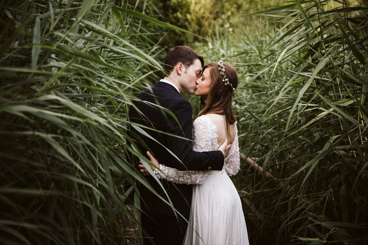 Bride in Emma Beaumont Wedding Dress and Groom in Dark Suit Kissing in the Long Grass