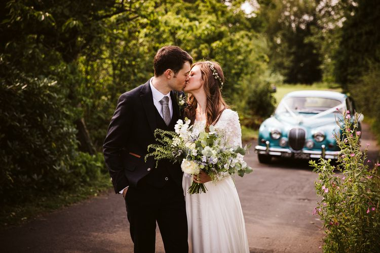 Bride in Emma Beaumont Wedding Dress and Groom in Dark Suit Kissing with a Vintage Blue Car in the Background.