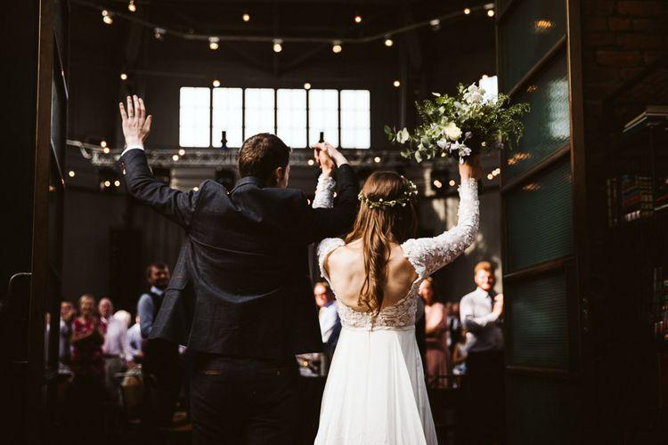 Bride in Emma Beaumont Wedding Dress and Groom in Dark Suit Entering the Wedding Reception