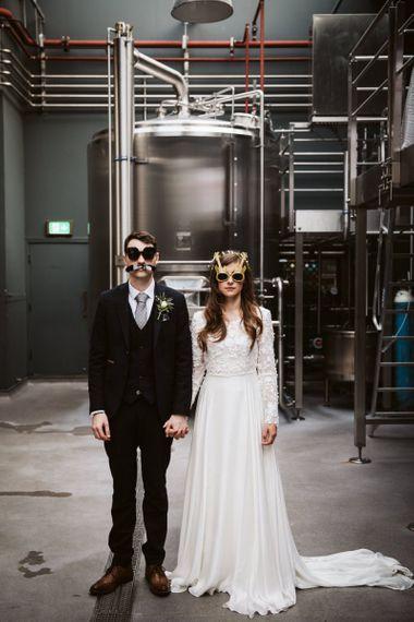 Bride in Emma Beaumont Wedding Dress and Groom in Master Debonair Suit  Wearing Masks